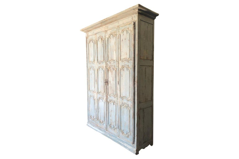 An outstanding and grand scale French Louis XIV period armoire soundly constructed from painted wood. The door panels are double hinged for easy interior access. The doors have beautifully sculpted panels. An exquisite cabinet. Terrific finish and