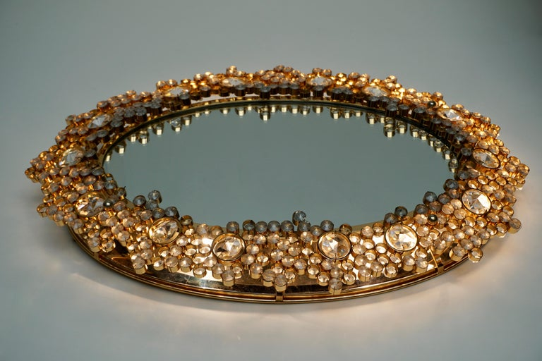 1970s illuminated oval mirror surrounded by a gold gilded frame that has numerous cut crystals. 