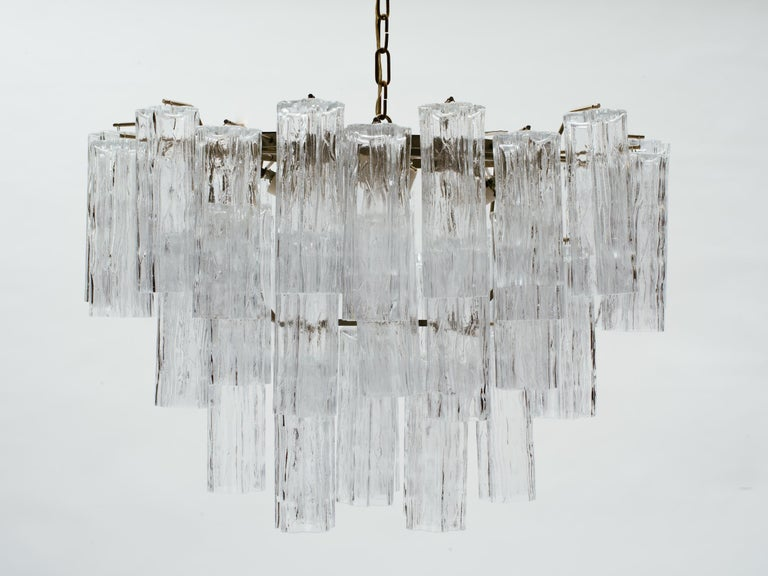 Large oval Italian glass tube tiered chandelier in the manner of Venini. Steel frame body hangs from link chain, labeled Made In Italy. Chandelier body measures 18