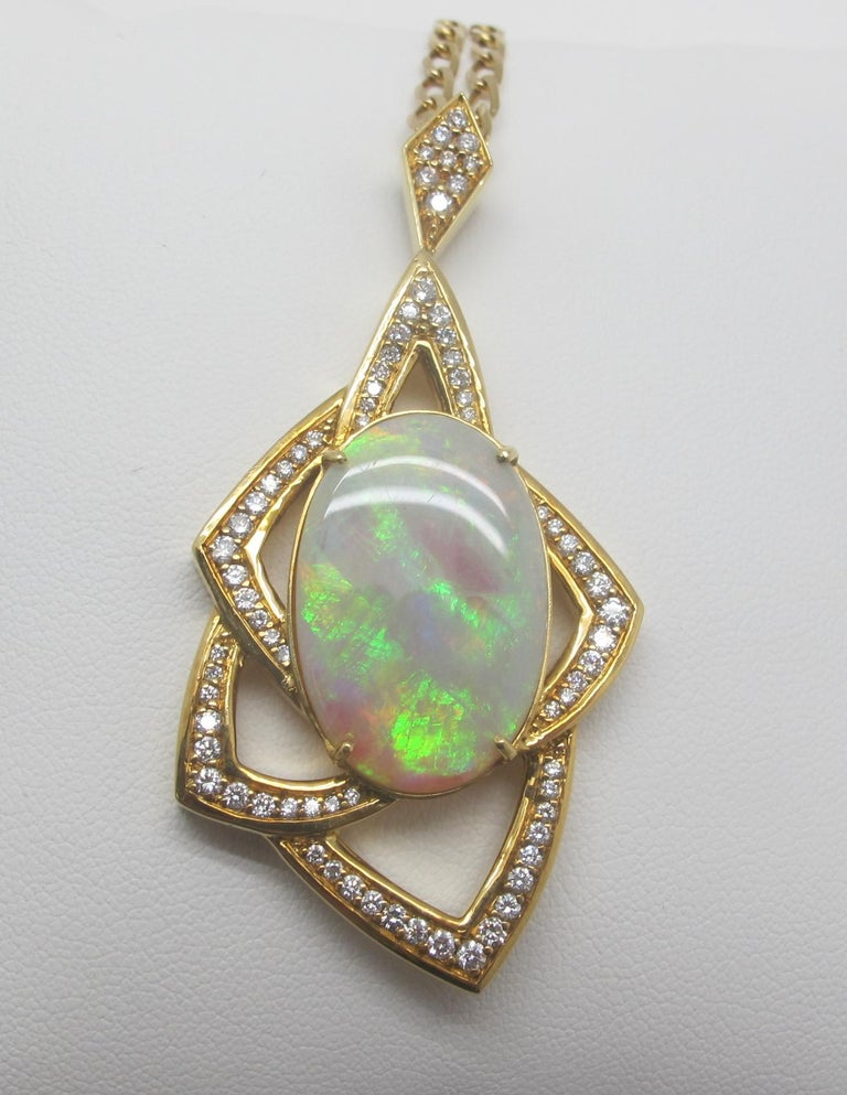 A very large Australian Opal, measuring  25.20x16.66x4.61mm is set with 64 round brilliant cut diamonds weighing a total of  1.50cts.  The opal is translucent with bright patches of green, yellow and red play-of- color.  This retro-style  pendant is