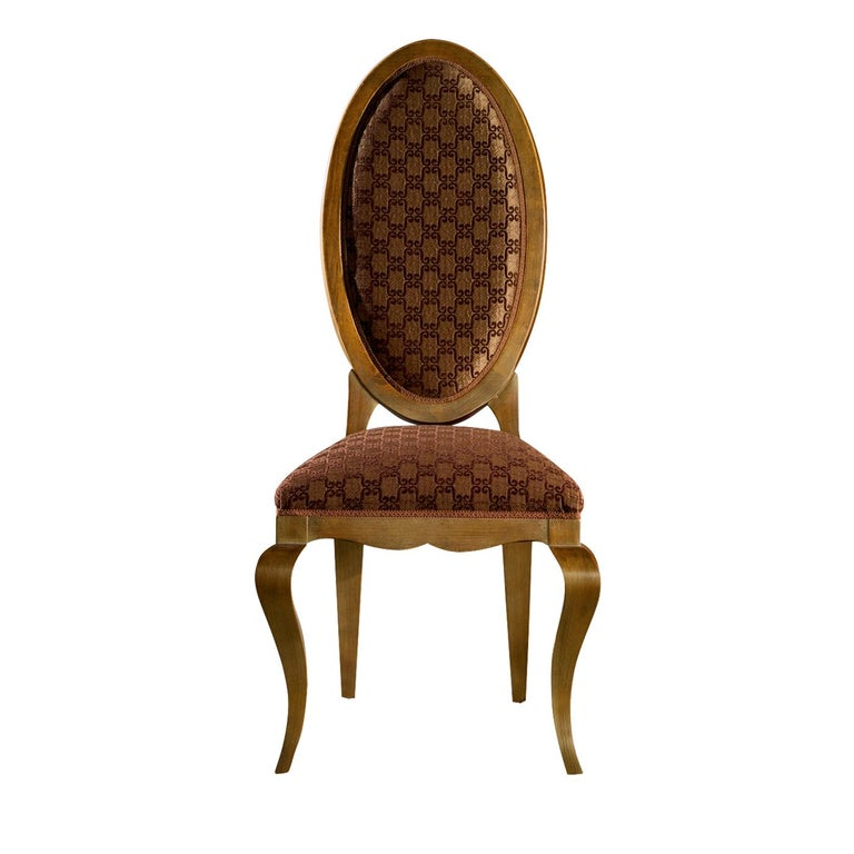 From the contemporary collection, this classic and elegant chair has a wooden frame and features a prominent oval-shaped back that gives the entire seat a slender and tapered form. The seat and back are padded and upholstered in fabric in shades of