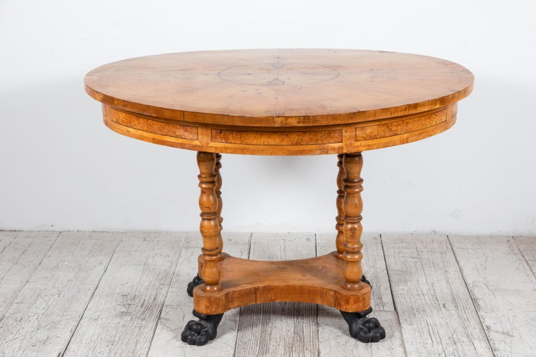 Oval Biedermeier style table with burl wood marquetry and clawfoot details.