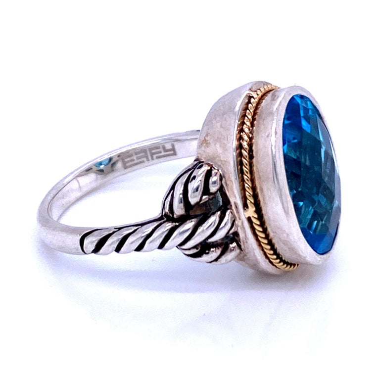One sterling silver and 18 karat yellow gold (stamped 18K 925 EFFY) ring set with one 14 x 10mm oval blue topaz set in a silver bezel with 18 karat yellow gold edge rope design on the shoulders.  The shank measures 2.2mm near the top of the ring and