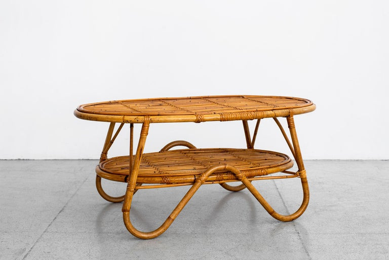 Italian rattan coffee table with curved legs and shelf.