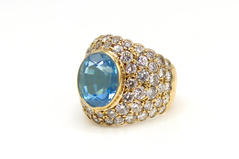 This uniquely designed, bold and  interesting ring from the 1980s,  was masterfully hand-crafted in 18 karat yellow gold. The wide half-band features bezel-set Santa Maria color oval brilliant cut Aquamarine measured to weigh over 6 carats and has