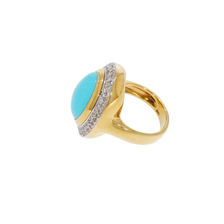 This alluring turquoise ring is centered with an oval cabochon-cut turquoise measuring 16x13mm, framed by a double row of pave-set round brilliant cut diamonds, weighing approx. 1.00 carats, the width of the band is 4.5mm. The ring is in great
