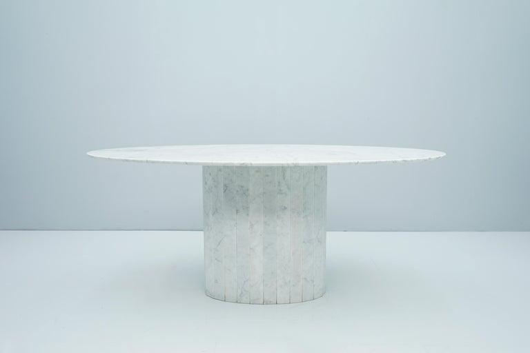 Beautiful oval dining table in white Carrara marble. The tabletop has been resealed and polished with epoxy resin. The table has no damage and no repairs. The table dates back to the 1970s and comes from Italy.