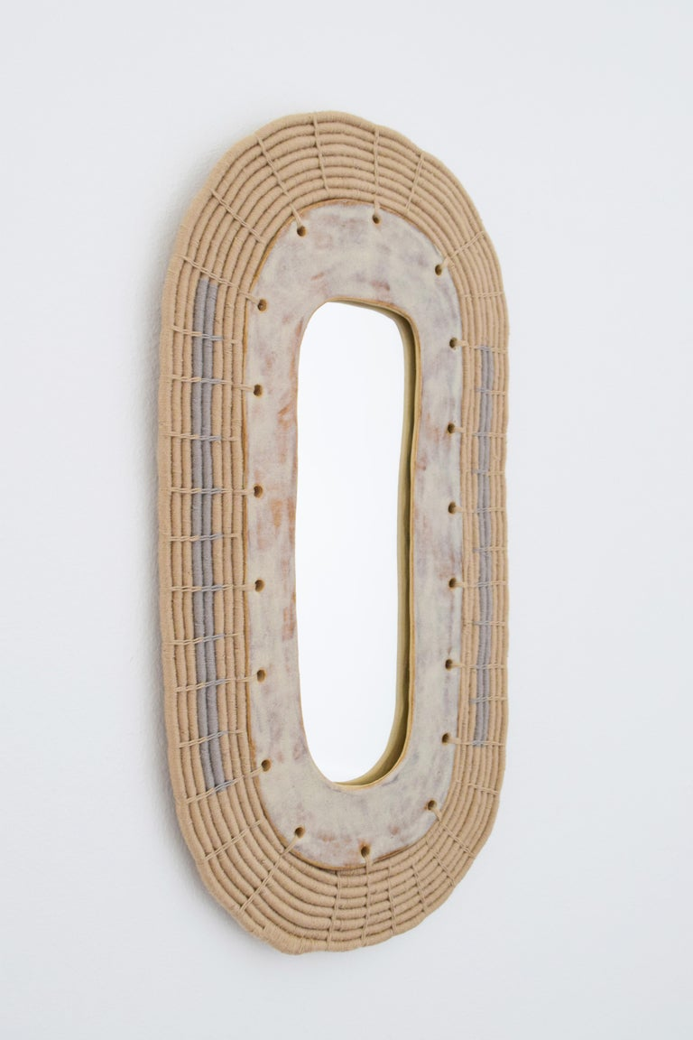 Made to order mirror #603 by Karen Gayle Tinney  Small oval mirror with ceramic plate surrounded by woven cotton. The perfect size to be hung alone, or as multiples on a wall. Ceramic plate is glazed in a shiny speckled gray/neutral glaze - each