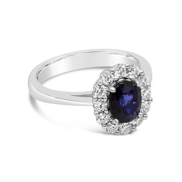 Showcasing a 1.60 carat oval cut blue sapphire, surrounded by a single row of round brilliant diamonds. Diamonds weigh 0.54 carats total. Made in 18 karat white gold.  Style available in different price ranges. Prices are based on your selection of