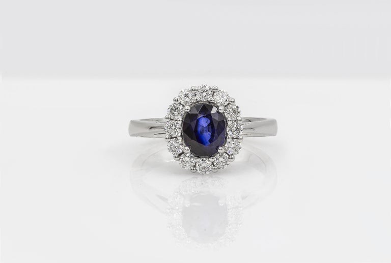 Contemporary Oval Cut Blue Sapphire and Diamond Halo Engagement Ring For Sale