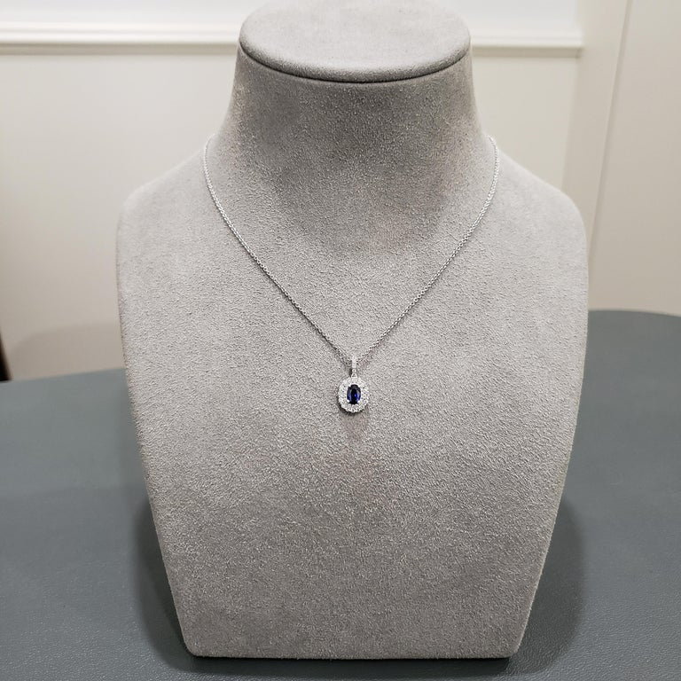 A simple pendant necklace showcasing a 0.52 carat blue sapphire, complemented by a round brilliant diamond surround. Diamonds weigh 0.37 carats total. Made in 18 karat white gold.  Style available in different price ranges. Prices are based on your