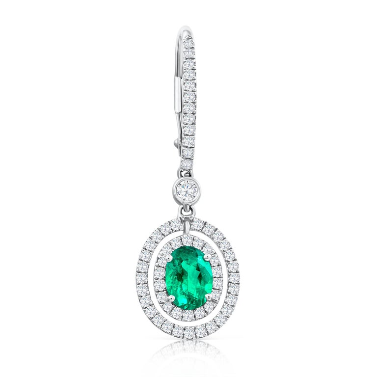 Classic 18k white gold dangle earrings set with 2 oval cut green emeralds weighing 1.01 carats total. The emeralds are surrounded by 2 rows of brilliant round diamonds weighinf 0.63 carats suspended on an accented lever-back. Spaced by a bezel set