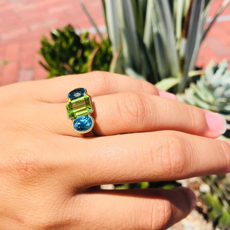 Contemporary Oval Cut Zircon and Emerald Cut Peridot 18 Karat Gold Ring For Sale
