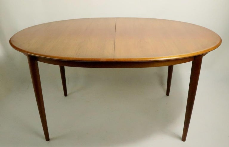 Large oval Danish Modern teak dining table which opens to accept two leaves (19 5/8 inch W each ) The table is in very good original condition, the top shows some tonal variation on the top surface, please see images. Table W without leaves 59 x 98