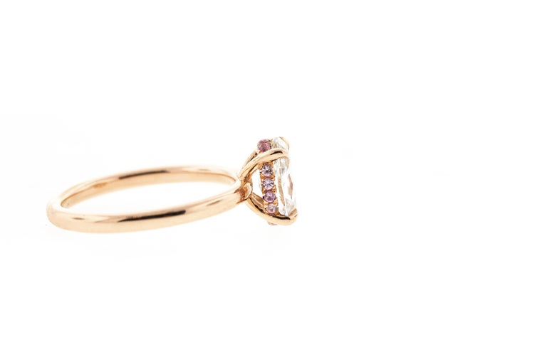 This rose gold engagement ring features an oval diamond for its center stone. A head-on shank setting with a hidden halo of pink sapphires encircles the center diamond. Made in rose gold, this ring can be customized in any color metal.