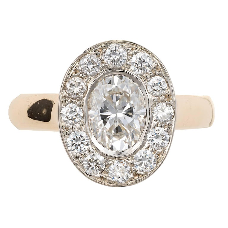 Oval diamond halo engagement ring in a solid 14k yellow gold setting, with a white gold top set with bright white shiny full cut diamonds surrounding an Ideal cut oval diamond 1.02ct. A wedding band fits flush against the side.  1.02ct oval diamond