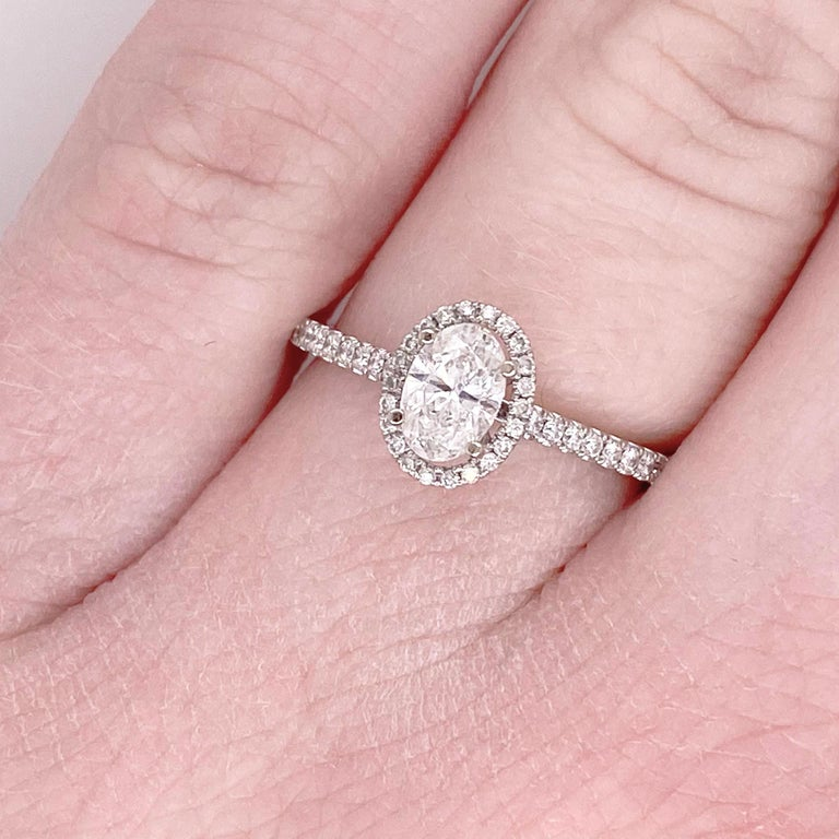 This stunning oval diamond set it 14k white gold and dripping with smaller diamonds is sure to take your breath away! This ring provides a look that is very modern yet classic. This ring is very fashionable and can add a touch of style to any