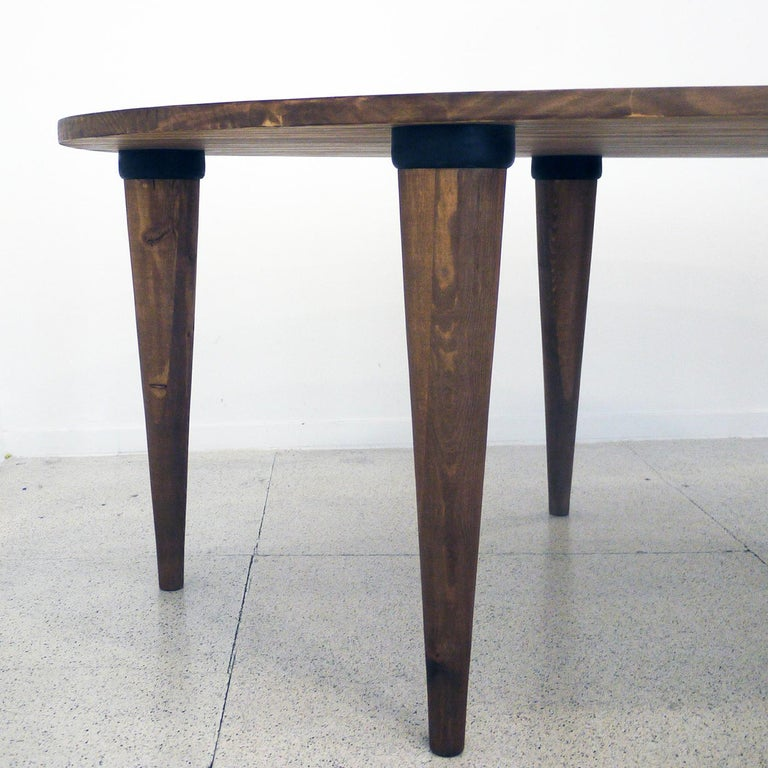 This elegant dining table is crafted from pine laminate with a rich walnut stain. Its spacious oval top sits upon six solid Alder wood legs, boasting streamlined conical silhouettes. Exuding a simple yet modern elegance, the Oval Dining Table