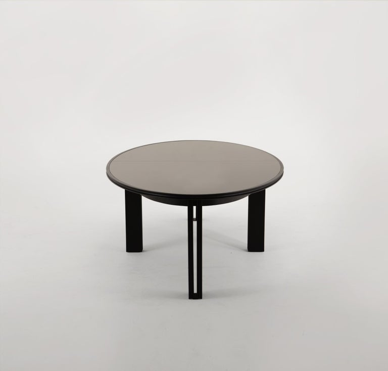 Vivien's table is crafted from a solid dyed oak tabletop, encasing two pieces of bronze glass that sit on eight hardwood oak legs. A concave profile carves the edges of the tabletop, and follows down the interior and exterior of the eight legs. The