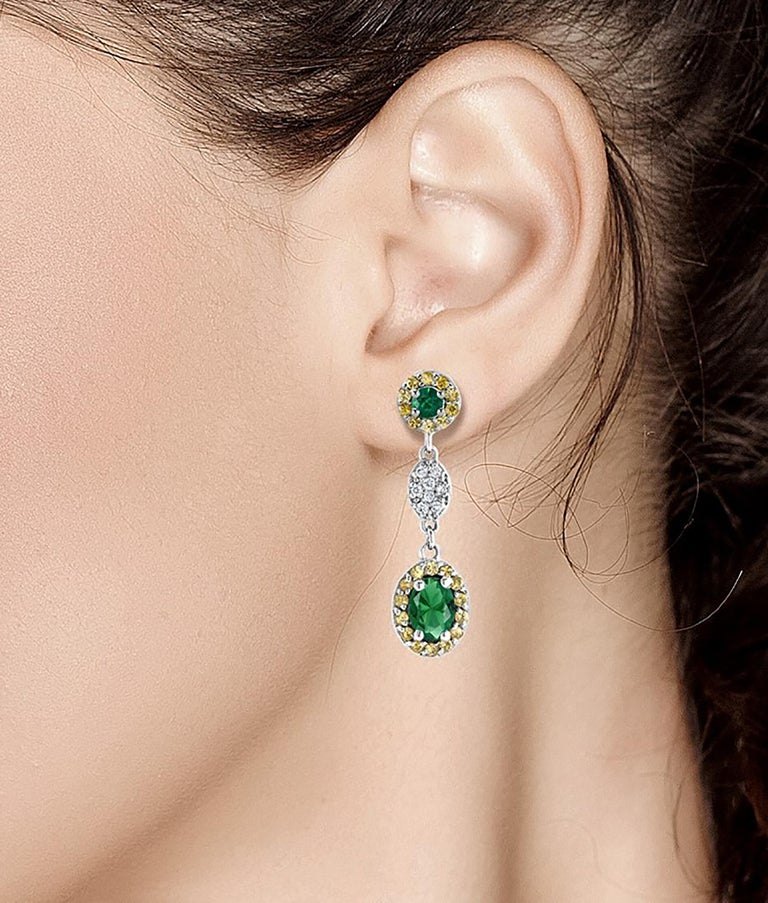 Fourteen karat white gold drop earrings with oval emerald, yellow sapphire and diamonds Oval emerald weighing 1.10 carat  Diamond weighing 0.20 carat  Yellow Sapphire weighing 0.35 carat  Earrings measuring one inch long  One of a kind earrings  New