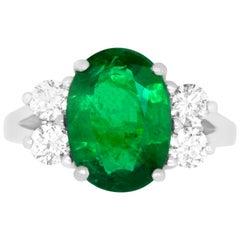 Oval Emerald and Diamond Side Stone Engagement Ring Split Shank 18K White Gold
