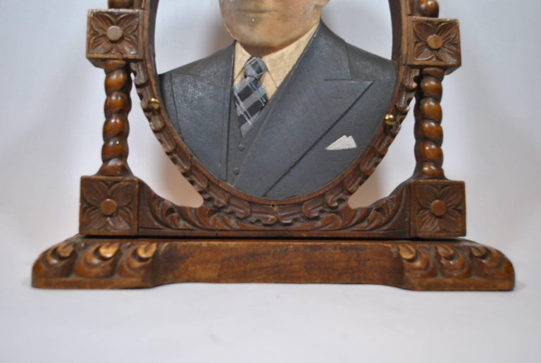 This object consists of hand-carved wooden busts with highly detailed carved and painted garment pieces accompanied by enlarged hand-painted photographed of deceased (in most cases) family members. This piece was commissioned from a collective of