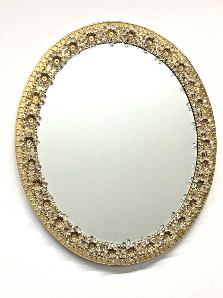 Stunning midcentury oval shaped glass mirror by German manufacturer Palwa. The gilt brass frame is decorated with delicate flowers made from faceted crystals and beads. The centre of the flower is finished with a gold - plated detail bolting the