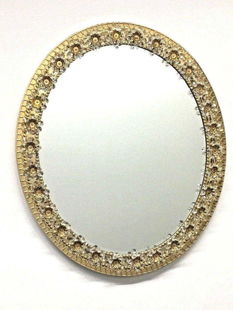 Stunning midcentury oval glass mirror by German manufacturer Palwa. The gold-plated brass frame is decorated with delicate flowers made from faceted crystals and beads. The centre of the flower is finished with a gold-plated detail bolting the
