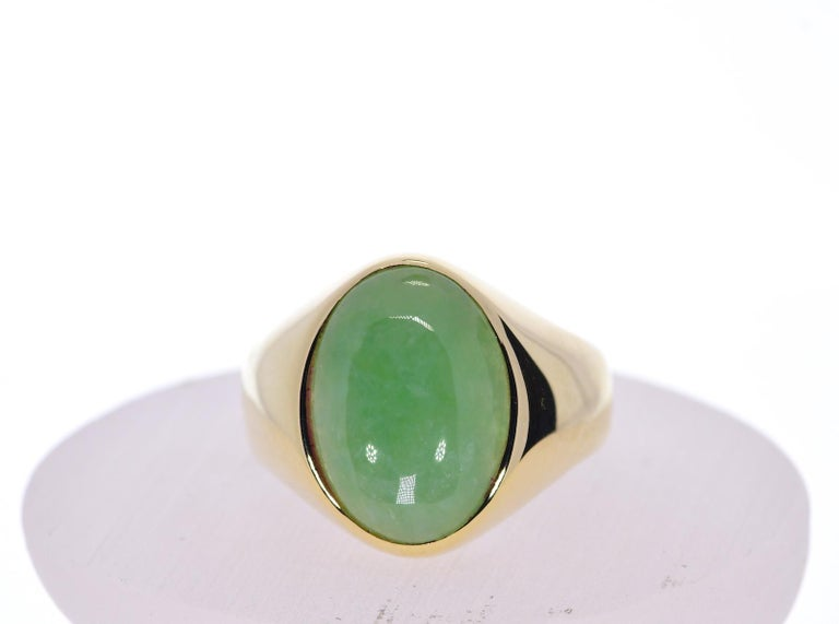 Oval Green Jade in 14k Yellow Gold 12 grams  Stone: Jade   Color: Mossy Green Semi Translucent    Shape:  Oval Metal: Yellow Gold Purity: 14k Total Gram Weight: 12 Ring Size 12 ( Please Inquire For Additional Sizing)      JESSUP'S PRICE:
