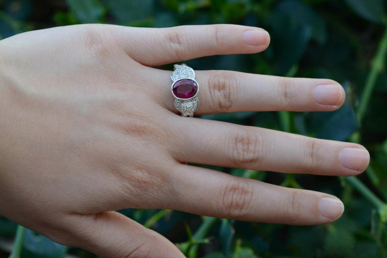 A most intriguing and vibrant, vintage pink tourmaline engagement ring set within a bezel is accompanied by a symphony of glimmering white diamonds in the crossover band. Lovingly crafted of 18K white gold, you'll love the way it sits low on your