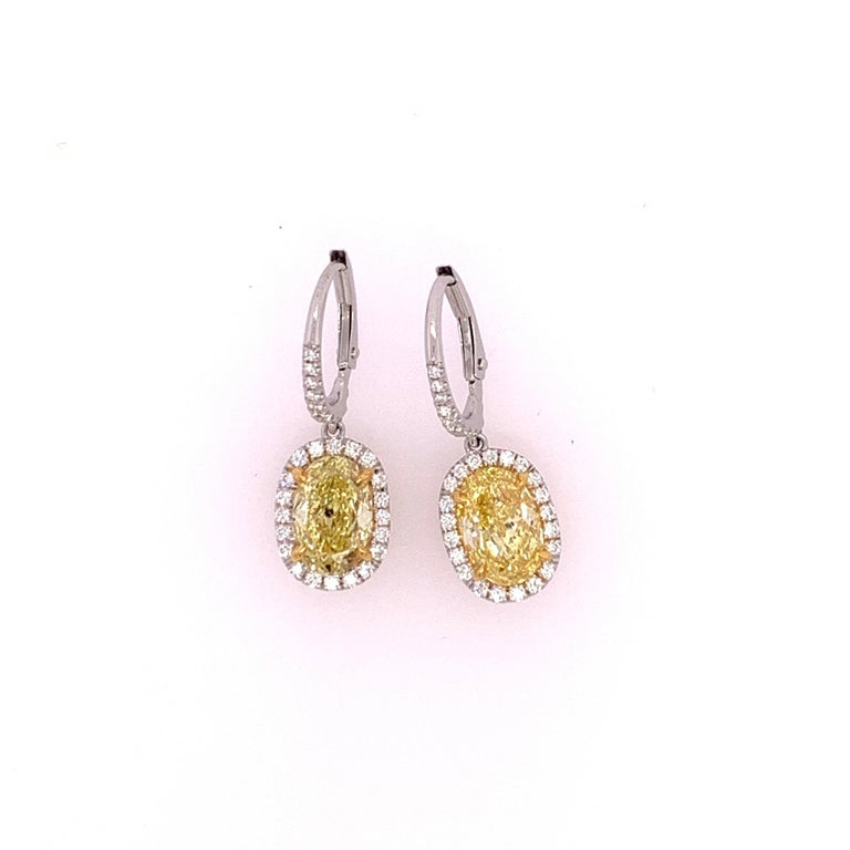 Platinum diamond earrings set with 0.42cts of colorless round brilliant diamonds. The yellow ovals are natural strong canary color. The cut on these Ovals are ideal proportions making it look larger than its weight, each stone has the measurements