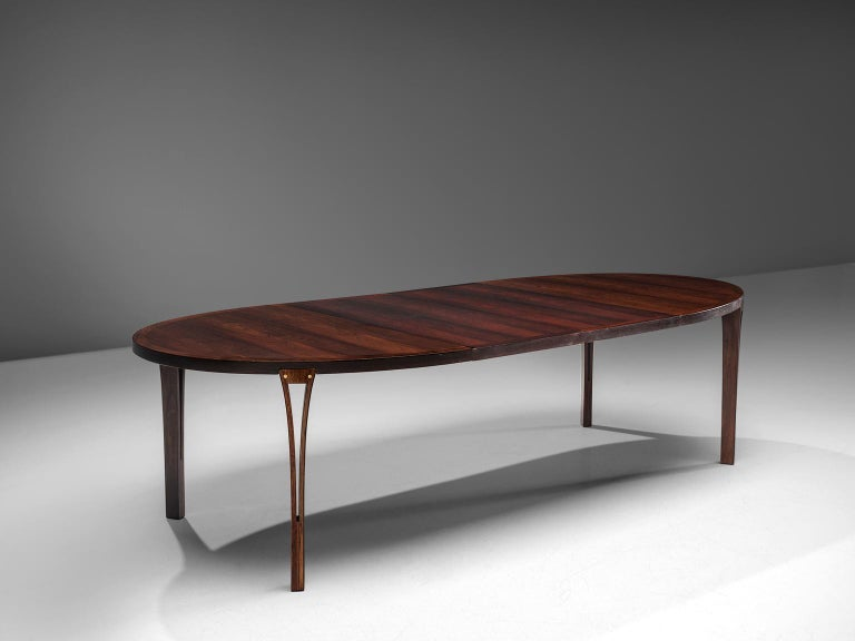 Dining table, rosewood, brass, Denmark, 1960s.  This exceptional dining table with extension leaves features four tapered circular legs beautifully spared into the plinth. The top shows an expressive rosewood grain, which gives it a warm look. The