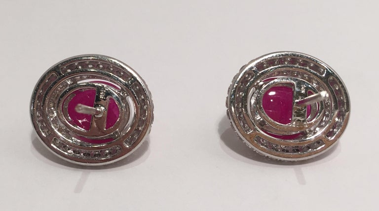 Contemporary Striking 3 Carat Oval Ruby Cabochon Triple Diamond Halo White Gold Post Earrings For Sale
