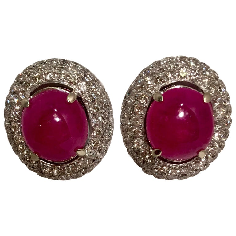 Striking 3 Carat Oval Ruby Cabochon Triple Diamond Halo White Gold Post Earrings For Sale
