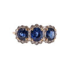 Oval Sapphire and Diamond Halo Trilogy Ring in 18 Carat Yellow Gold