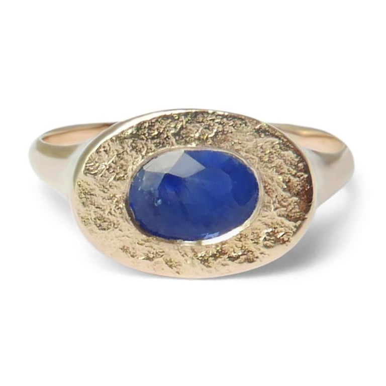 This textured signet ring features a natural oval-shaped Sri Lankan sapphire embedded in a shimmering texture crafted in solid 14-carat gold.  The ring is finished with a high polish on the sides and band for a comfortable fit.  This ring is a UK