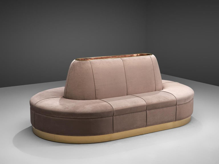 Oval sofa, velvet, brass, Italy, 1970s  This oval shaped sofa is arranged around a center piece with integrated storage space. At the bottom from a gold colored brass base the velvet upholstery starts its way upwards. The upholstery is structured in