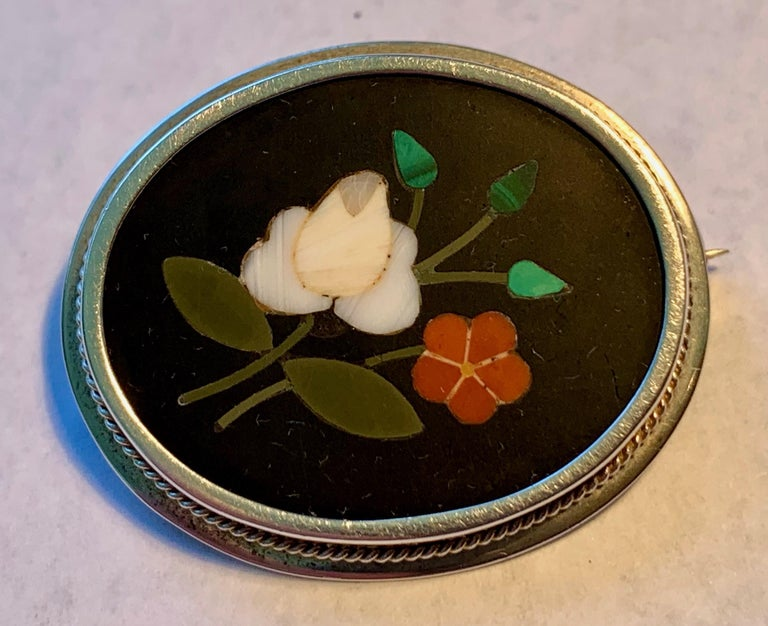 Victorian oval .800 silver pietra dura brooch with a pin stem locking back.  The black ground shows off a white rose with buds and another flower.   Simple and sweet.  The dark ground is probably onyx inlaid with hardstones and various semi-precious
