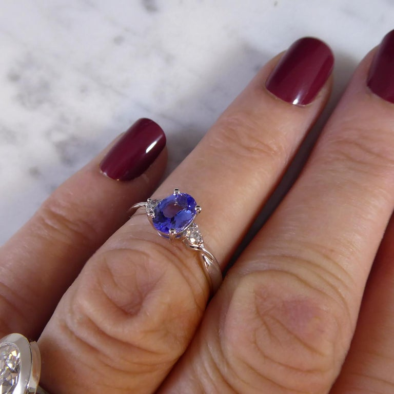 A very pretty three stone ring set with an oval tanzanite measuring 7.0mm x 5.0mm in white four claw setting.  To each side a brilliant cut diamond (total diamond weight 0.10ct) three claw set to twisted shoulders to D shaped, cross-sectioned