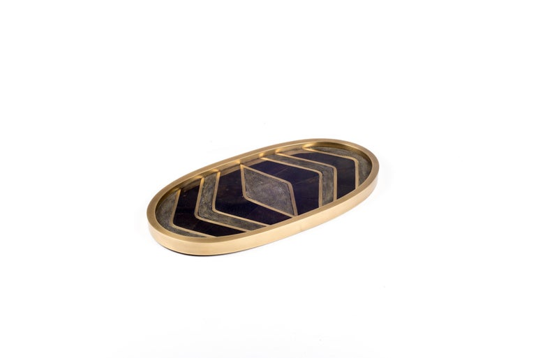 A Classic oval vanity tray revisited; this Kifu Paris tray is inlaid cream shagreen, making for a stunning tabletop piece in any space. The frame is inlaid in bronze-patina brass. Available in other finishes and a rectangle shape.