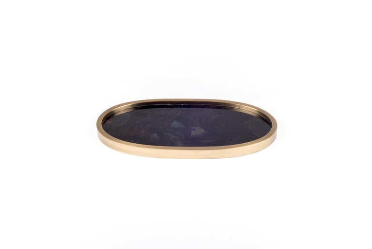 A classic oval vanity tray revisited; this Kifu Paris Tray is inlaid in blue pen shell that has incredible color tonalities in it, making for a stunning tabletop piece in any space. The frame is inlaid in bronze-patina brass. Available in other