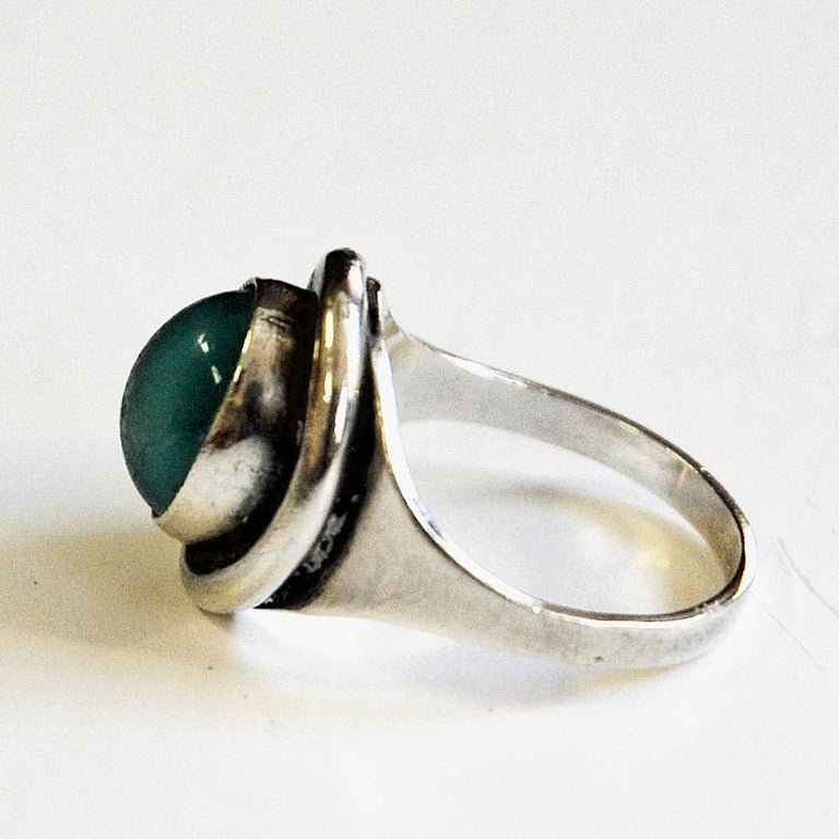 Decorative and lovely vintage silvering with a shiny medium oval turquoise stone designed by Sven Holmström, Sweden, 1960s.  Stamped: 935 and SH. Measures: Inner diameter is 16.5 mm, Size of stone: 10 mm x 8 mm. Scandinavian design. Very nice and