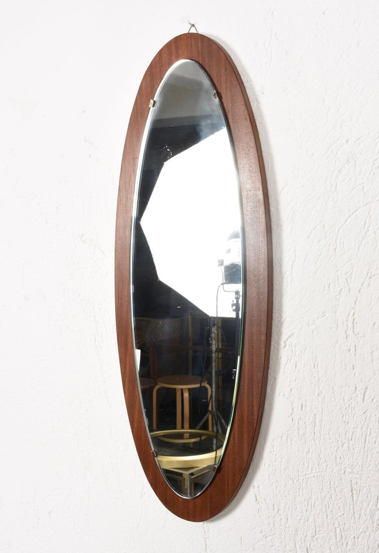 Italian oval wall mirror from the 1960s. The base is in mahogany, the supports that hold the mirror in solid brass. The conditions are good. Measures: 87 x 34 cm.