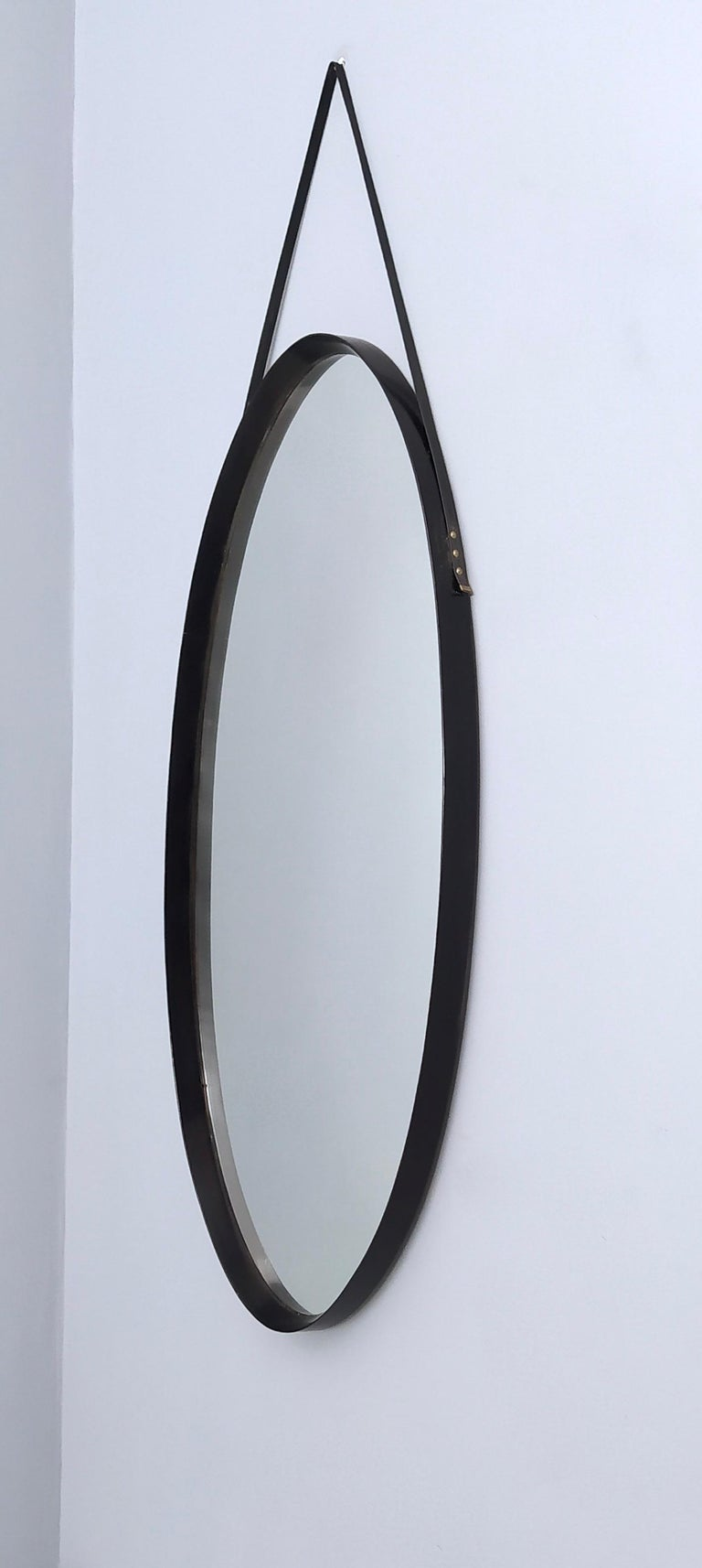 Oval Wall Mirror with Ebonized Wood Frame and a Leather Hook, Italy In Good Condition For Sale In Bresso, Lombardy