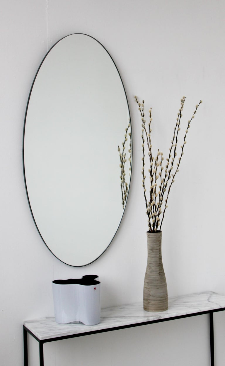 Delightful handcrafted silver oval mirror with a black frame. Designed and made in London, UK.  Measures: W 480 x H 970 x D 18 mm  We supply in custom size, mirror tint or frame finish, and offer bevelling as an option.  Mirror tints