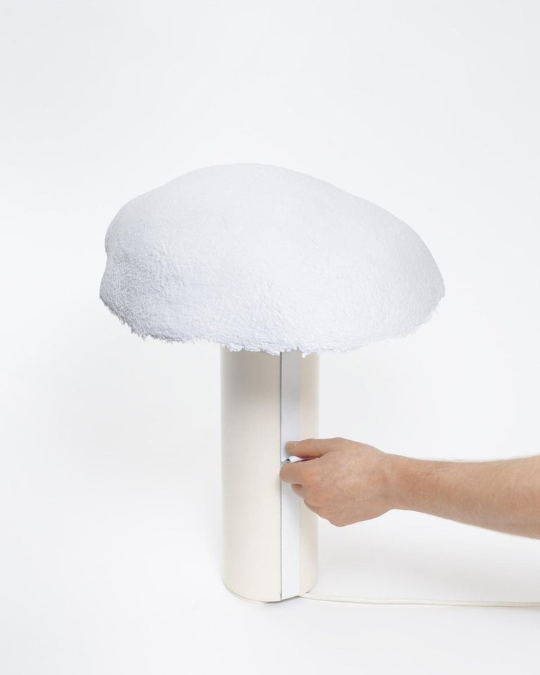 The overcast light consists of an aluminum cylindrical base and a paper shade. The shade is Handmade from blended paper pulp that allows light to shine through mimicking the effect of the sun obscured by cloud cover. Every shade's lower rough hewn