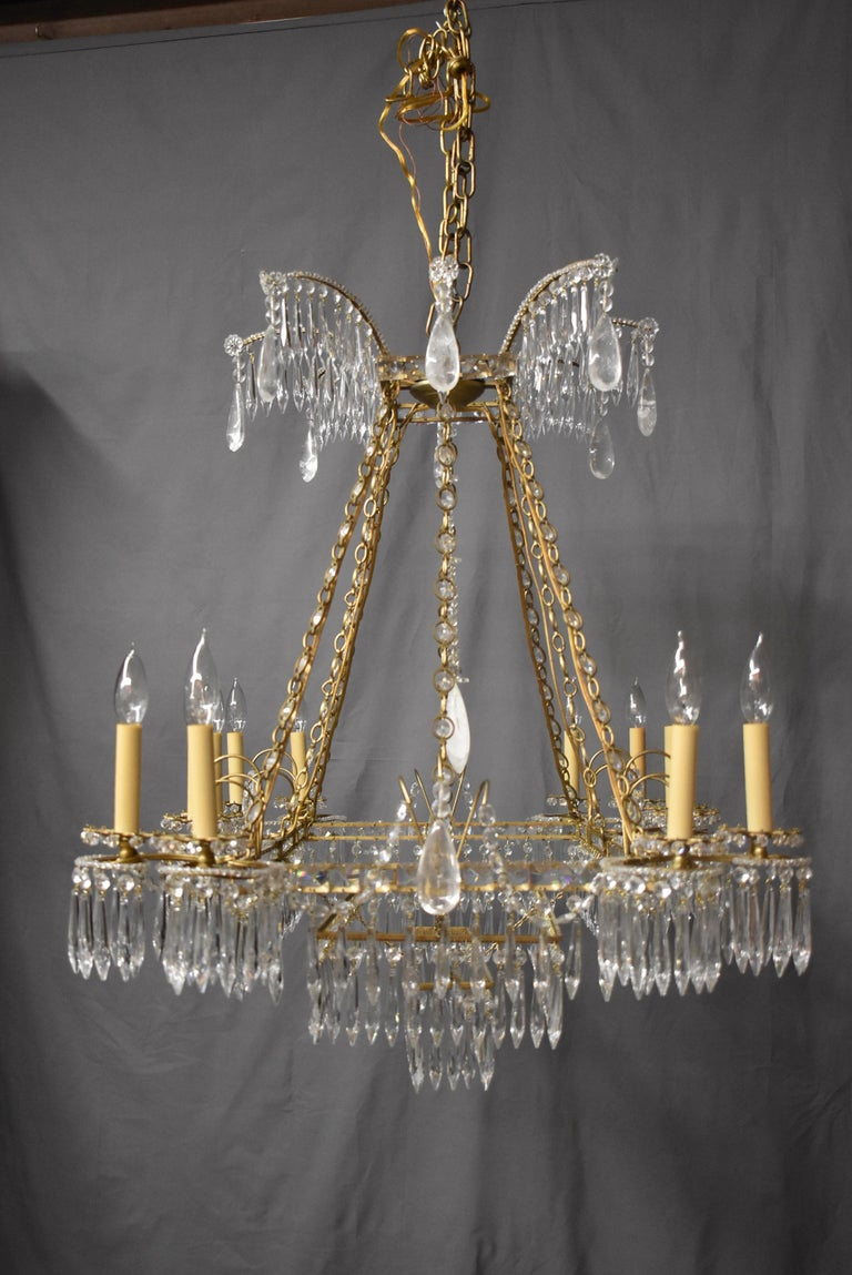 An incredible French style crystal and brass chandelier. This beautiful oversize fixture features 12 sockets and three lower tiers of crystals on the bottom. The dimension are 43