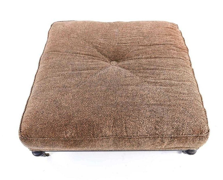 Large generous sized upholstered square ottoman covered in faux leopard print with a center tuft has a low wood base with turned legs and brass casters. Ottoman is a great coffee table size. Search terms: Edwardian style ottoman, tufted
