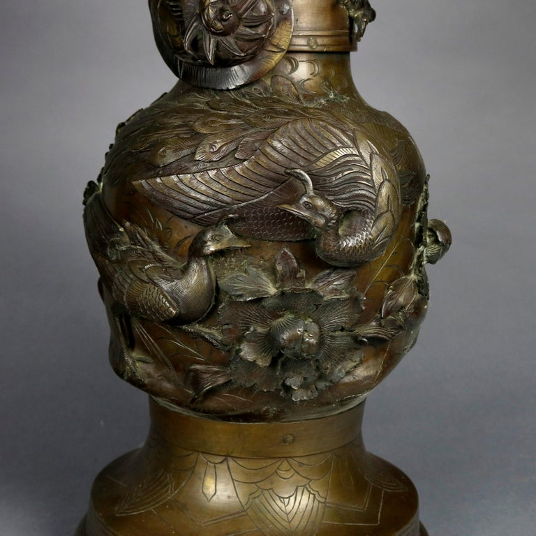 An oversized antique floor vase offers bronze floor vase offers urn form with all-over high relief garden scene with flowers, birds, and dragon on neck, incised Greek Key pattern on collar and base, circa 1920  ***DELIVERY NOTICE – Due to COVID-19