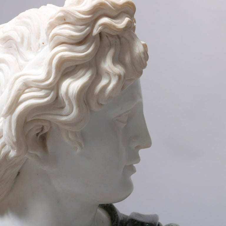 An oversized Italian carved marble portrait sculpture depicts the classical Greek bust of David after Michelangelo, seated on round plinth, 20th century